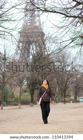 Beautiful young tourist in Paris near the Eiffel Tower