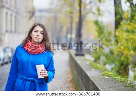 Beautiful young tourist in Paris on a fall day, drinking coffee to go - stock photo