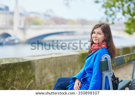 Beautiful young tourist in Paris, sitting on the bench near the Seine