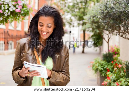 beautiful young tourist looking at map. - stock photo