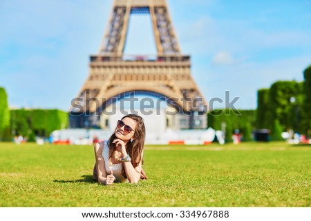 Beautiful young tourist or student girl in Paris sitting on the grass near the Eiffel tower on a summer day - stock photo