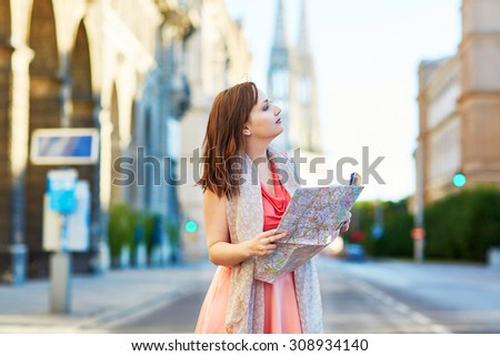 Beautiful young tourist walking in the street, using map and planning itinerary in Vienna, Austria - stock photo