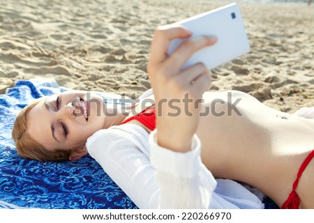 Beautiful young tourist woman on holiday relaxing on a beach and holding a smartphone device in her hands taking selfies pictures of herself, networking. Travel vacation technology outdoors. - stock photo