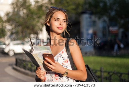 Beautiful young tourist woman using smart phone for navigation.