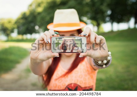 Beautiful young trendy Caucasian redhead woman taking a selfie with smart phone outdoors in park on sunny summer day. Closeup shot. Cute teenage girl with red hair posing for self portrait in nature. - stock photo