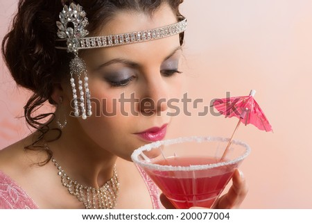 Beautiful young vintage 1920s woman with headband and flapper dress drinking a cocktail - stock photo