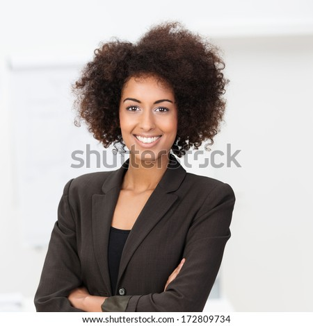 Beautiful young vivacious African American businesswoman in a stylish jacket standing with her arms folded beaming at the camera