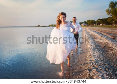 Beautiful young wedding couple at the shore - stock photo