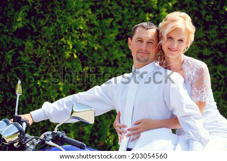 beautiful young wedding couple, blonde bride with flower on motorcycle with her groom