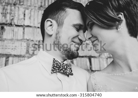 Beautiful young wedding couple is kissing and smiling in indoor. decorating studio.