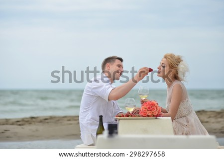 Beautiful young wedding couple of man and woman sitting on sea beach shore at table with rose bouquet eating red strawberry and drinking white wine from glasses copyspace, horizontal picture - stock photo