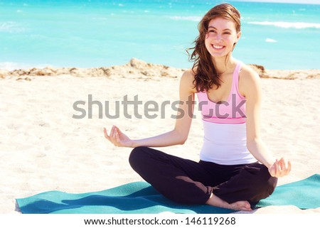 Beautiful young white female doing yoga at the beach