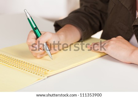 Beautiful young white woman working at desk wearing green casual jacket with long brown hair.