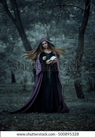 Beautiful young witch Halloween wearing vintage Gothic dress with hood keeps magic of an ancient book of spells in a mysterious forest.Fantastic shooting in the wild.Fashionable toning.Creative color