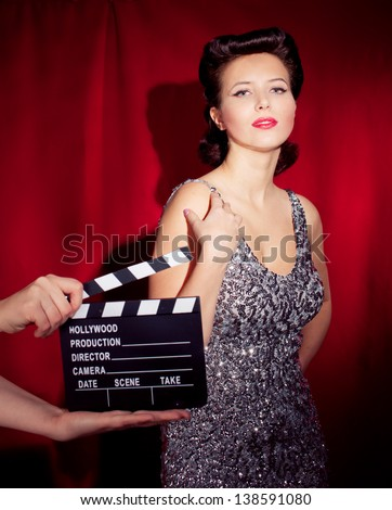 Beautiful young woman actress posing. Clapperboard . - stock photo
