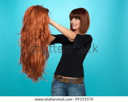 beautiful, young woman admiring a long, red hair wig she is holding, on blue background