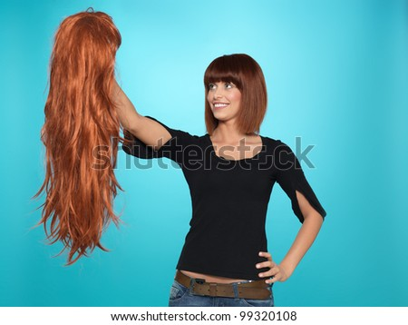 beautiful, young woman admiring a long, red hair wig she is holding, on blue background - stock photo