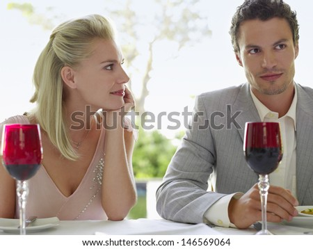 Beautiful young woman admiring man at dinner table - stock photo