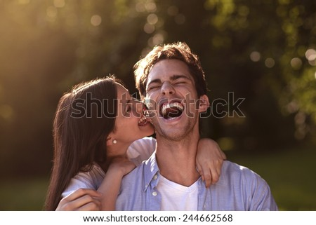 Beautiful young woman affectionately biting her boyfriend's ear in a park