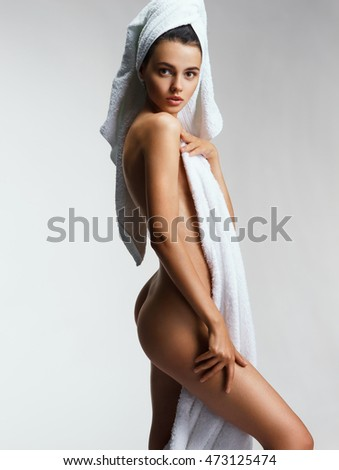 Beautiful young woman after bath with towel. Photo of Sexy body of beautiful woman on gray background. Beauty & Skin care concept