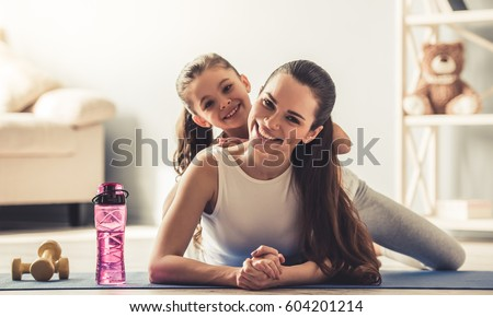 Beautiful young woman and charming little daughter are looking at camera and smiling while working out at home