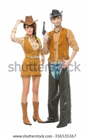 Beautiful young woman and handsome man looking like dolls dressed in cowboy costumes. Isolated over white background. Copy space.
