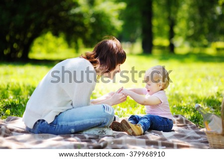 Beautiful young woman and her adorable little son having a picnic in sunny park