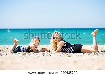 Beautiful young woman and her charming daughter resting on the beach  - stock photo