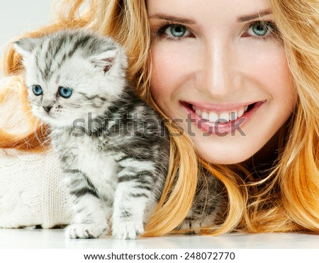 Beautiful young woman and her little kitten. Cute kitten. - stock photo