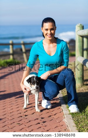 beautiful young woman and her pet dog at the beach - stock photo
