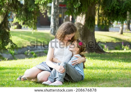 beautiful young woman and little girl sitting on grass, against green of summer park.