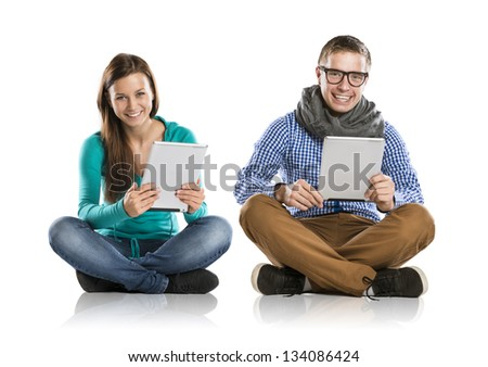 Beautiful young woman and man with tablet in studio - stock photo