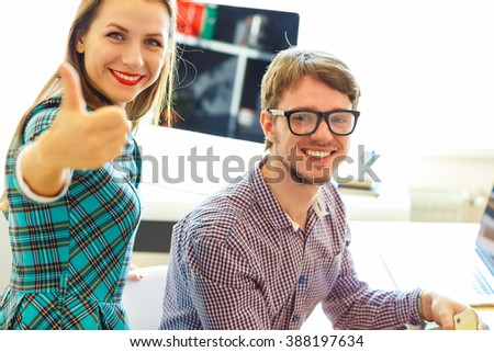 Beautiful young woman and man with thumb up in office - modern business concept