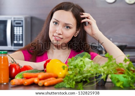 Beautiful, young woman and vegetables in the domestic kitchen - stock photo
