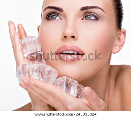 Beautiful young woman applies the ice to face. Skin care concept.  - stock photo