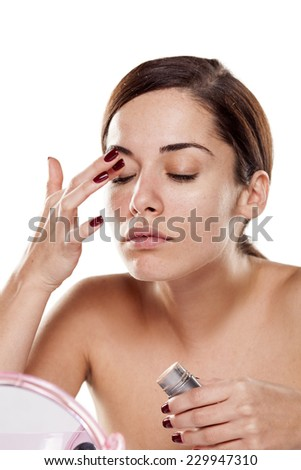 Beautiful young woman apply concealer around her eyes - stock photo