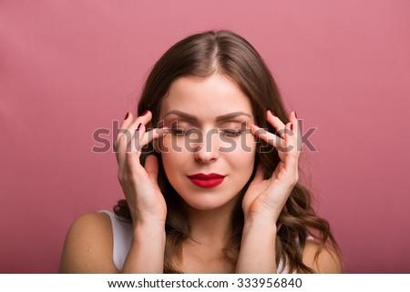 Beautiful young woman applying an eye cream - stock photo