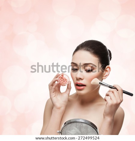 Beautiful young woman applying blush to her cheeks with special blusher brush. Isolated on pink coral background. Square composition. Copy space. - stock photo