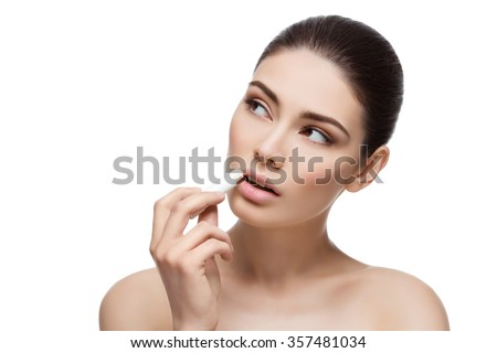 Beautiful young woman applying chapstick to lips. Isolated over white background. Copy space. - stock photo