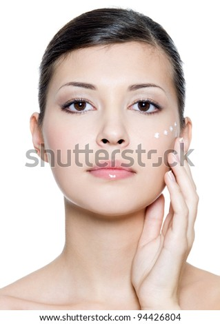 Beautiful young  woman applying cosmetic  cream around the eye . Isolated on white background