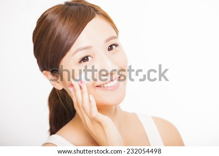beautiful young woman applying cosmetic cream  on her face - stock photo