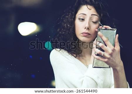 Beautiful young woman applying cosmetic eyeshadow brush make-up - stock photo