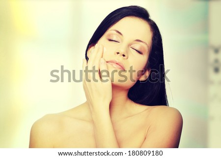 Beautiful young woman applying cream on her face.  - stock photo
