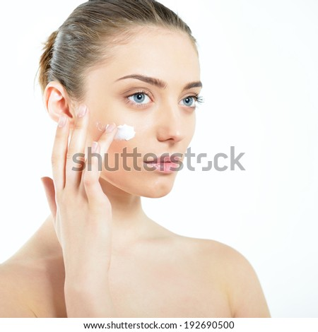 Beautiful young woman applying cream on her face. Girl with perfect skin. - stock photo