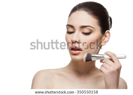 Beautiful young woman applying face powder with dual fiber brush. Isolated over white background. Copy space.
