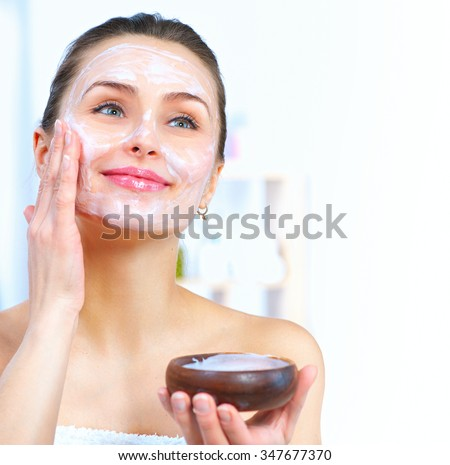 Beautiful Young Woman applying facial homemade Mask at home. Spa and skin care concept - stock photo