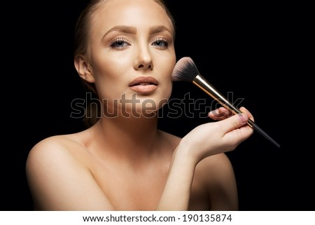 Beautiful young woman applying foundation on her face with a makeup brush isolated on black background. Attractive young caucasian model. - stock photo