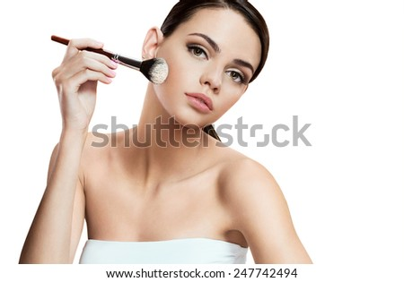 Beautiful young woman applying foundation on her face with tassel, skin care concept / photo composition of brunette girl  - isolated on white background  - stock photo