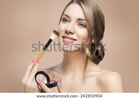 Beautiful young woman applying foundation powder or blush with makeup brush - stock photo