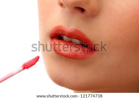 beautiful young woman applying lip gloss, isolated on white - stock photo